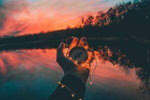 sunset, water, trees, hand holding compass, string lights on the hand