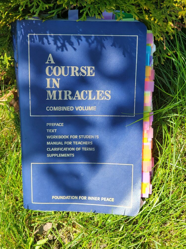 A Course In Miracles soft cover book with a grass background