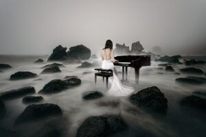 woman in a wedding dress, playing piano, fog on the ground, black and white, sad mood